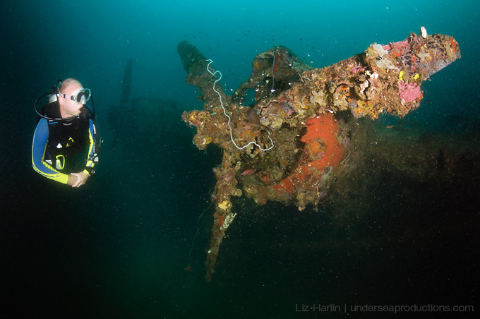 Underwater photograph of a scuba diver exploring the wreck of a WWII fighter plane.