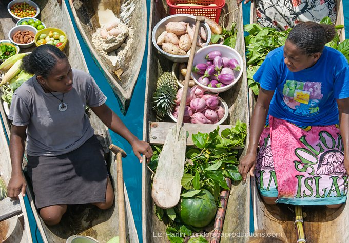 Two indigenous women sell vegetables from their dugout canoes, Solomon Islands