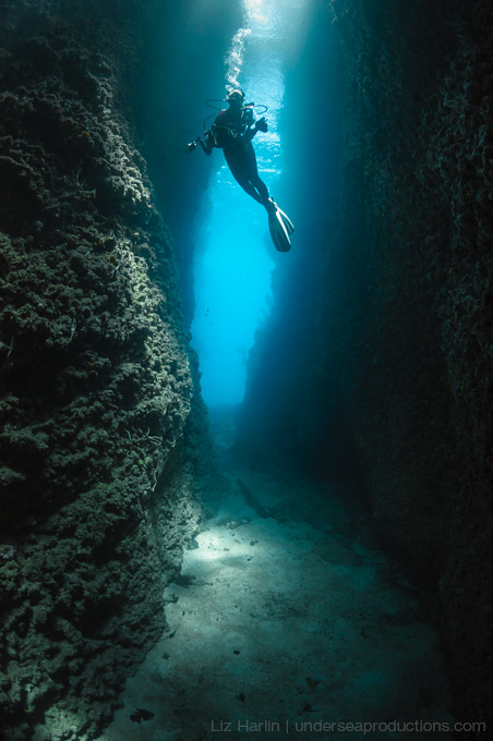 Underwater photograph of a scuba diver hovering in between two walls of an underwater cut / crevice.