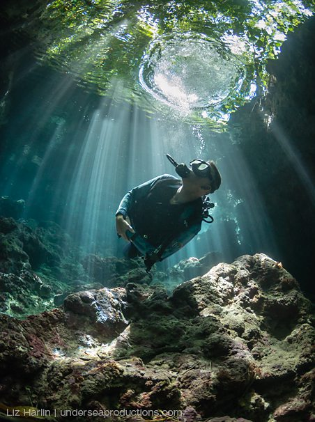Underwater photo of a scuba diver looking up at the light beams that filter through the water. Solomon Islands.