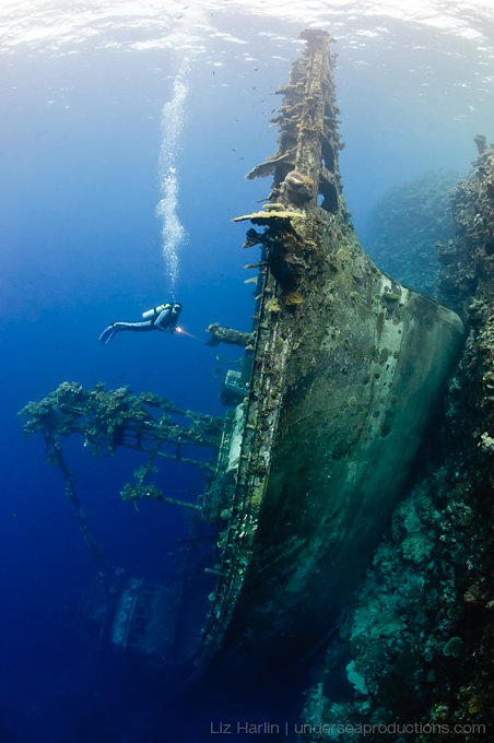 Underwater photograph of a scuba diver exploring an unusually orientated shipwreck in the Solomon Islands