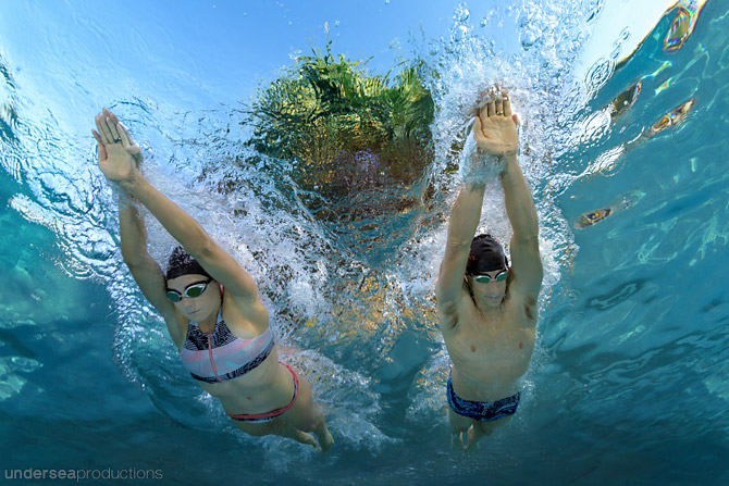 Underwater portrait of a male and female pair of triathletes gliding underwater, face down, passing overhead, in blue tropical water.