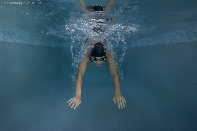Artistic underwater portrait of a female swimmer diving into pool