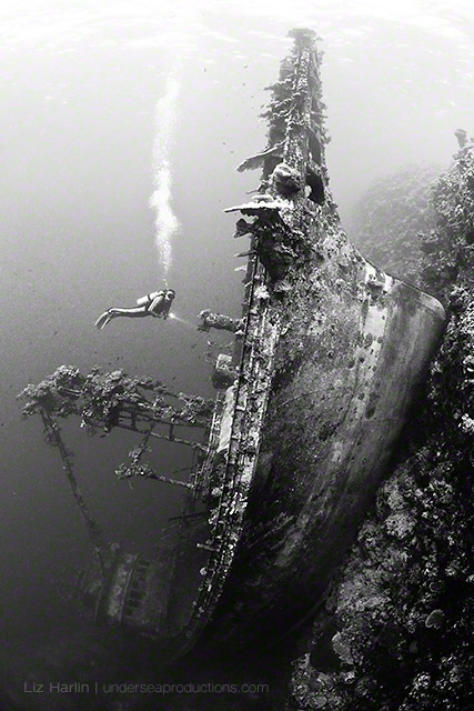 Black-and-white underwater photograph of a scuba diver exploring an upright shipwreck