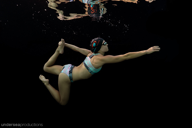 Underwater portrait of a swimming athlete, wearing swim goggles and swim cap and bikini, doing a strong pose against a black background, with relections in the water's surface above