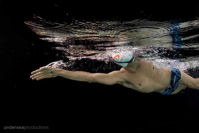 Underwater Lifestyle Portrait of Athlete Swimming hard through black water.