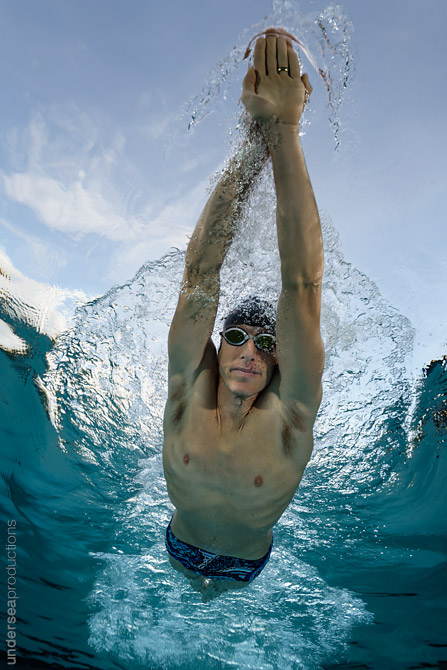 Underwater photo of a male swimming athlete gliding overhead with arms stretched forward, swimming through blue tropical water.