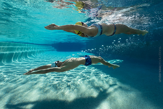 Underwater photo of a swimming couple gliding through a resort s