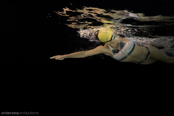 Underwater photograph of a female swimming freestyle through bla