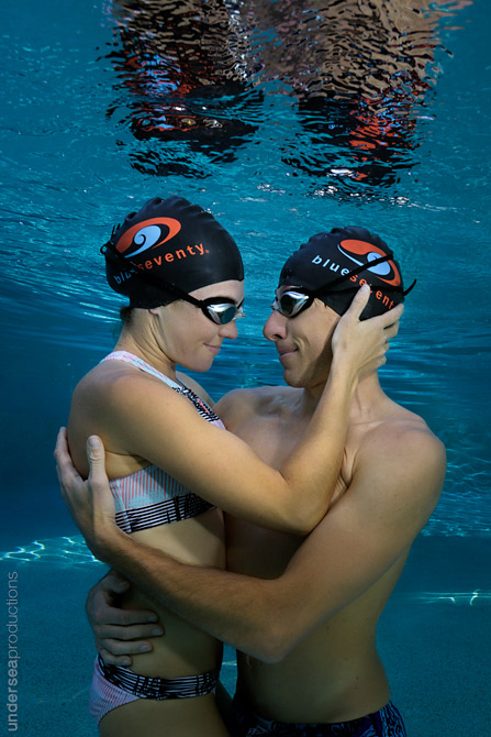Underwater portrait of a swimming couple embracing and looking into each other's eyes