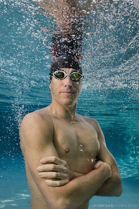 Underwater portrait of male swimming athlete surrounded by bubbl