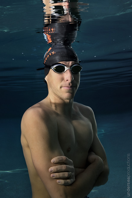 Portrait of a pro swimming athlete, standing underwater with arms crossed, wearing swim goggles and cap; his reflection shows in the water's surface above.