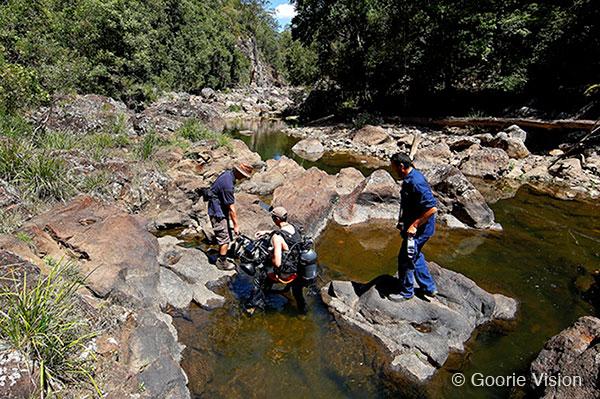 Film crew and underwater cameraman trekking through Obi Obi Gorge to find a filming location. Mary River, Queensland, Australia.