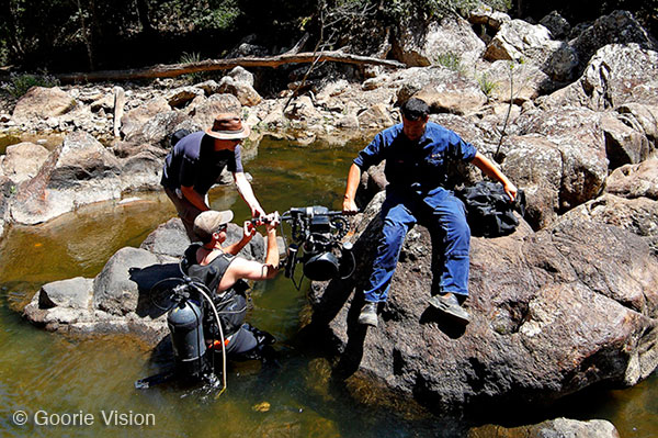 Film crew and underwater cameraman trekking through Obi Obi Gorge to find a filming location. Mary River, Queensland, Australia.