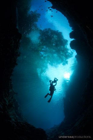 scuba diver silhouette in a cave with trees behind